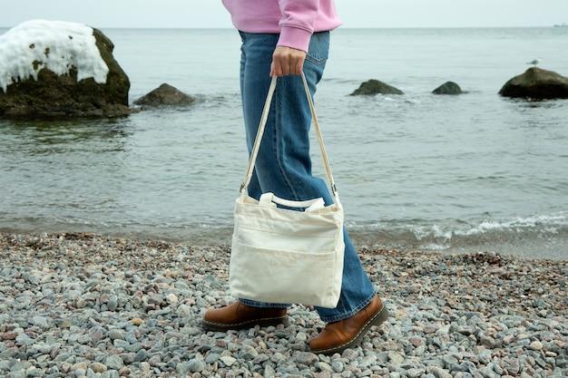 Young woman hold stylish eco bag on pebble beach