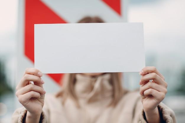 若い女性は手にホワイトペーパーポスターを保持します。手で白い空のテンプレートシートを持つ少女。