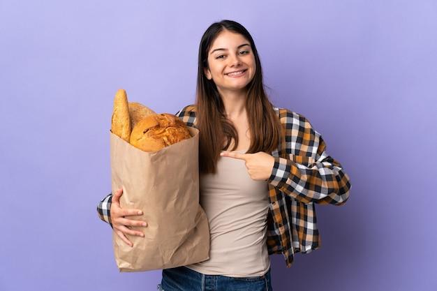 Молодая женщина держит сумку, полную хлеба, изолированную на фиолетовом и указывая на нее