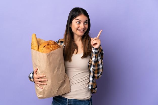 Молодая женщина, держащая мешок, полный хлеба, изолирована на фиолетовом, намереваясь найти решение, подняв палец вверх