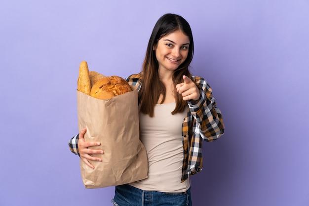 Молодая женщина, держащая сумку, полную хлеба, изолирована на фиолетовом, указывая пальцем на вас с уверенным выражением лица