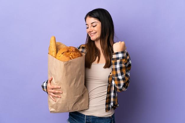 勝利を祝う紫色の壁に隔離されたパンでいっぱいのバッグを保持している若い女性