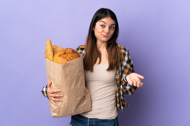 어깨를 들어 올리는 동안 의심 제스처를 만드는 보라색 벽에 고립 된 빵의 전체 가방을 들고 젊은 여자