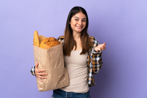 Молодая женщина держит сумку, полную хлеба, изолированную на фиолетовом, с шокированным выражением лица