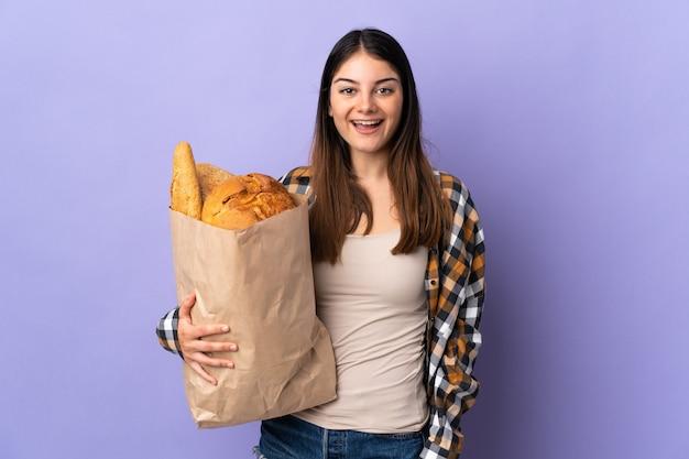 Молодая женщина, держащая сумку, полную хлеба, изолирована на фиолетовом, с удивленным и шокированным выражением лица