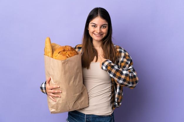Молодая женщина держит сумку, полную хлеба, изолированную на фиолетовом, с удивленным выражением лица