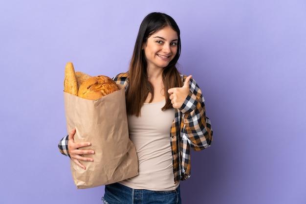 Молодая женщина держит мешок, полный хлеба, изолирован на фиолетовом, с большими пальцами руки вверх, потому что произошло что-то хорошее
