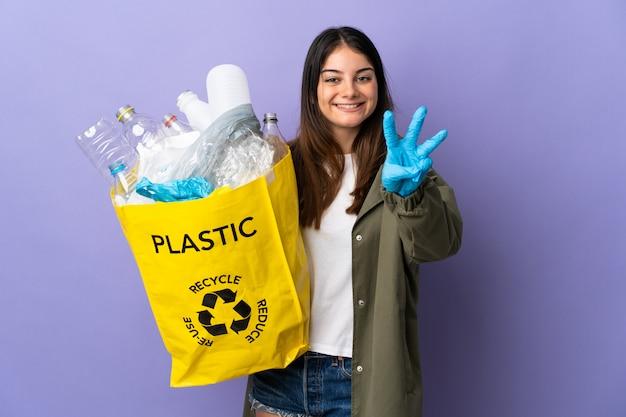 リサイクルするペットボトルの完全な袋を保持している若い女性は紫で分離され、指で3つを数える