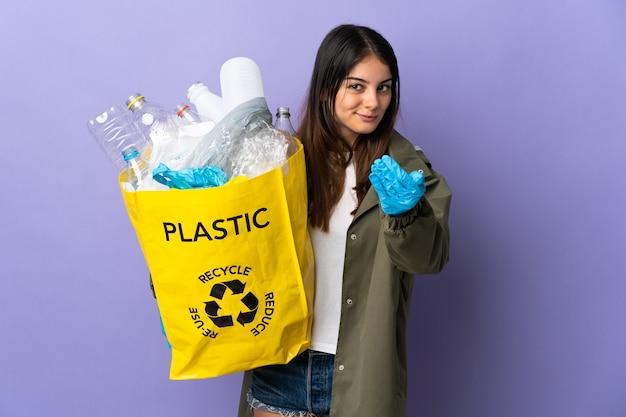 Молодая женщина, держащая мешок, полный пластиковых бутылок для переработки, изолирована на фиолетовом, приглашая прийти с рукой. счастлив что ты пришел