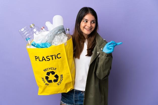 紫色の壁に隔離されたリサイクルのためにペットボトルでいっぱいのバッグを持っている若い女性は、指を持ち上げながら解決策を実現しようとしています