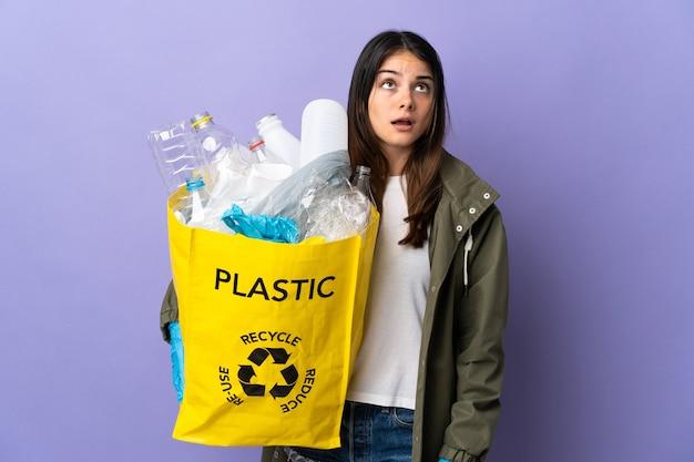 Молодая женщина, держащая сумку, полную пластиковых бутылок для переработки, изолирована на фиолетовой стене, глядя вверх и с удивленным выражением лица