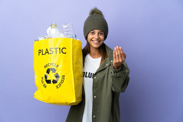 Молодая женщина, держащая мешок, полный пластика, приглашая прийти с рукой. счастлив что ты пришел