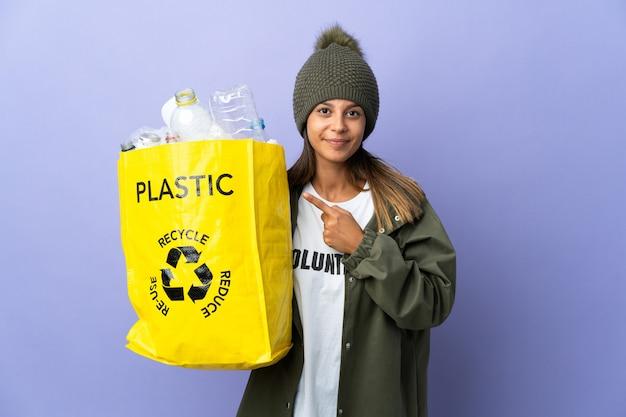 제품을 제시하기 위해 측면을 가리키는 플라스틱으로 가득 찬 가방을 들고 젊은 여자