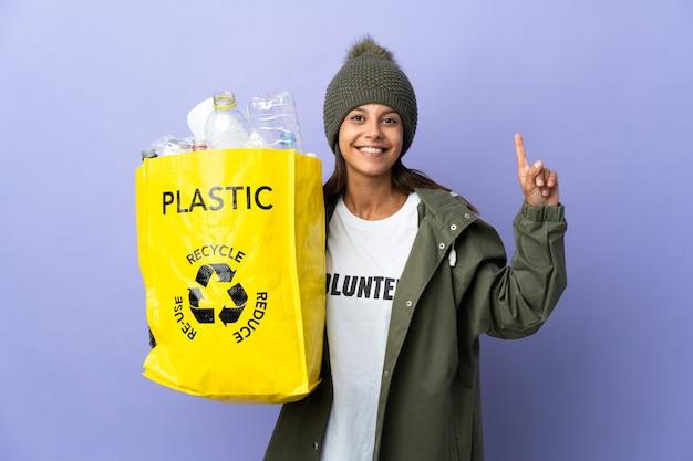 素晴らしいアイデアを指し示すプラスチックでいっぱいのバッグを保持している若い女性