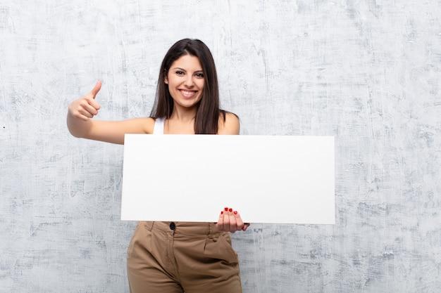 グランジの壁にバナーを保持している若い女性