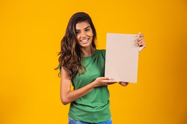 Молодая женщина держит знамя с пространством для текста.