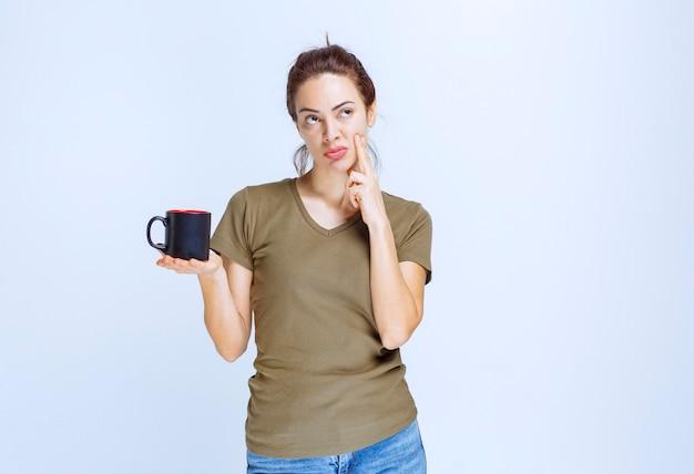 Молодая женщина держит чашку черного кофе и думает