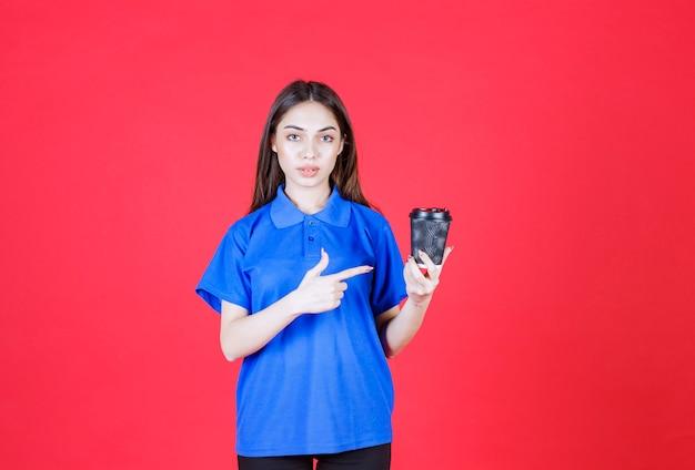 黒の使い捨てコーヒーカップを保持している若い女性