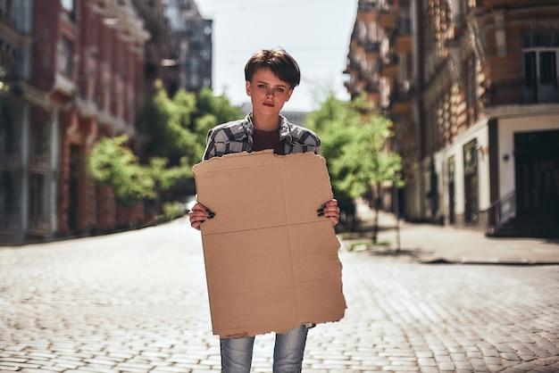 空白のバナーを保持し、道路に立っている間カメラを見ている若い女性