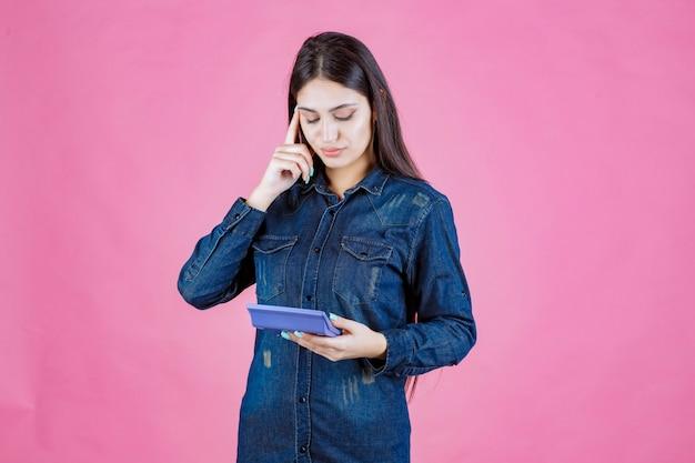 Молодая женщина держит синий калькулятор и думает