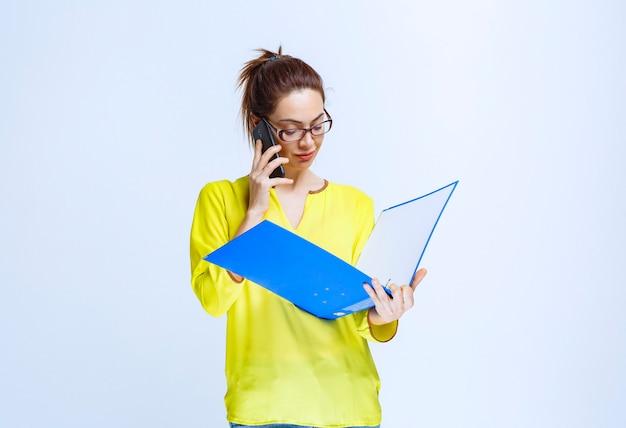 青いフォルダーを保持し、積極的に電話に話している若い女性