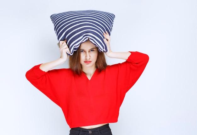 彼女の頭の上に青い縞模様の枕を保持している若い女性。