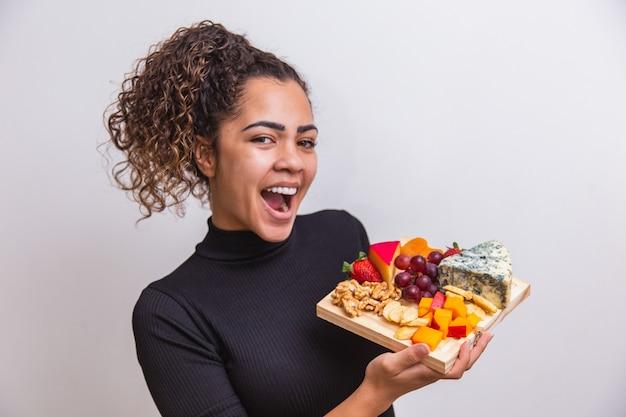 다양 한 종류의 스낵 치즈와 함께 보드를 들고 젊은 여자.