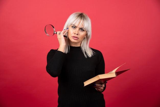 빨간 벽에 부분 확대 책을 들고 젊은 여자.