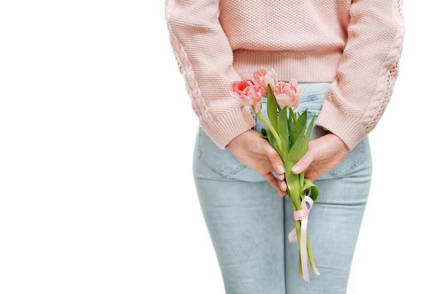흰색 배경에 등 뒤에서 분홍색 튤립 꽃다발을 들고 있는 젊은 여성. 텍스트 공간, 선택적 초점.