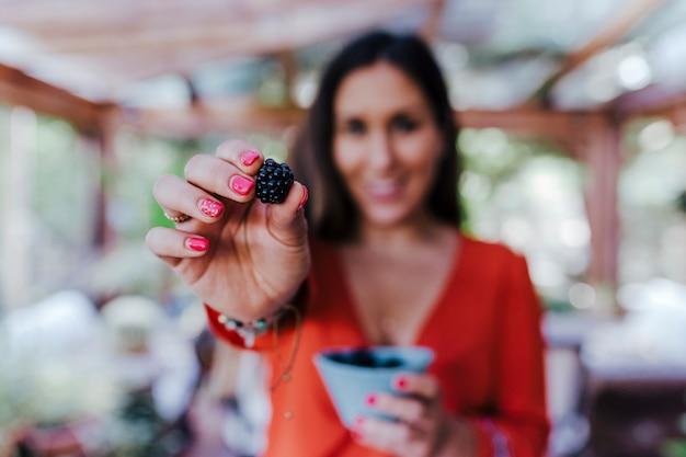 ブラックベリーのボウルを保持している若い女性。多様な果物、スイカ、オレンジ、ブラックベリーの健康的なレシピを準備しています。ミキサーを使用します。自家製、屋内、健康的なライフスタイル。セレクティブフォーカス