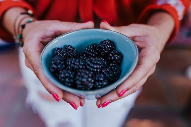 ブラックベリーのボウルを保持している若い女性。多様な果物、スイカ、オレンジ、ブラックベリーの健康的なレシピを準備しています。ミキサーを使用します。自家製、屋内、健康的なライフスタイル