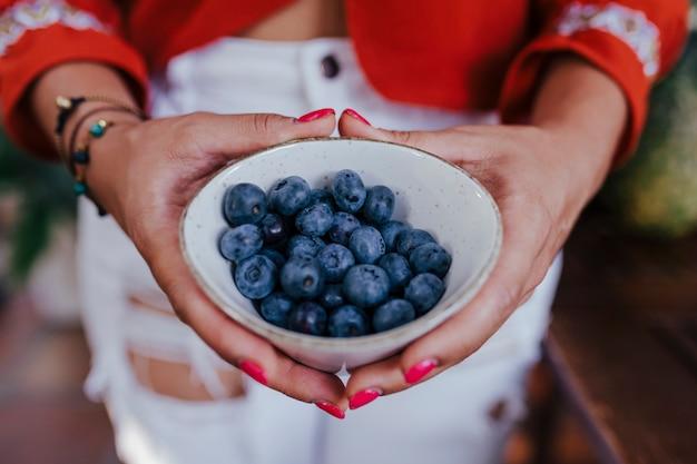 ブルーベリーのボウルを保持している若い女性。多様な果物、スイカ、オレンジ、ブラックベリーの健康的なレシピを準備しています。ミキサーを使用します。自家製、屋内、健康的なライフスタイル