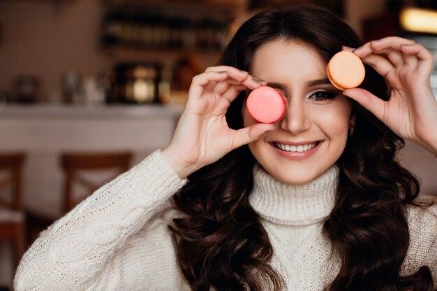 Молодая женщина держит кучу разноцветных миндальных печений вокруг ее лица