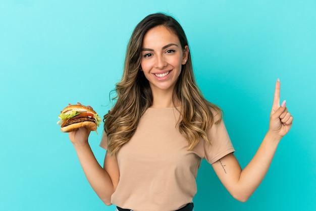 고립된 배경 위에 햄버거를 들고 있는 젊은 여성이 최고라는 표시로 손가락을 들고 들어올린다