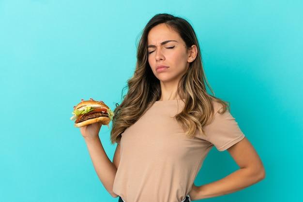 Молодая женщина, держащая гамбургер на изолированном фоне, страдает от боли в спине из-за того, что приложила усилия