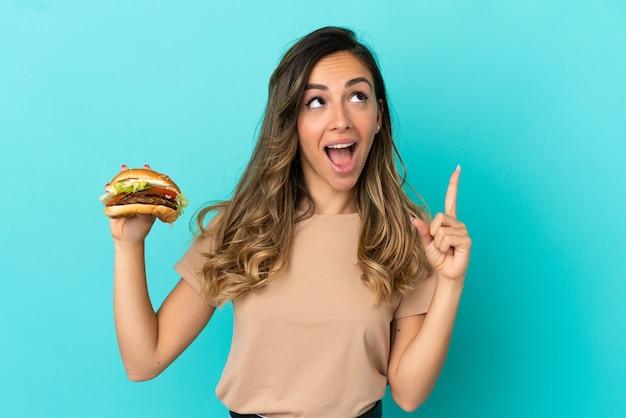 Молодая женщина, держащая гамбургер на изолированном фоне, думает о идее, указывая пальцем вверх