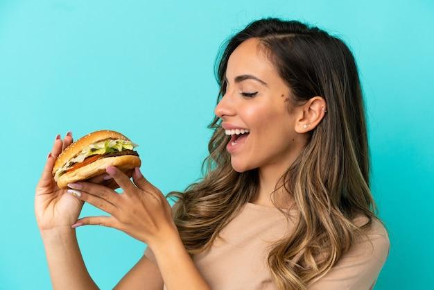 Молодая женщина, держащая гамбургер на изолированном фоне
