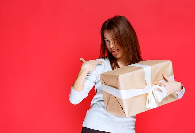 Молодая женщина, держащая картонную подарочную коробку, выглядит удивленной и позитивной