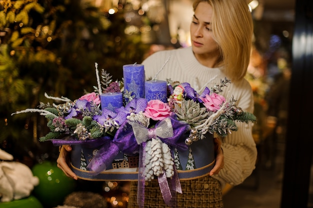Молодая женщина держит рождественскую композицию с фиолетовыми и розовыми цветами, суккулентами, еловыми ветками и свечами
