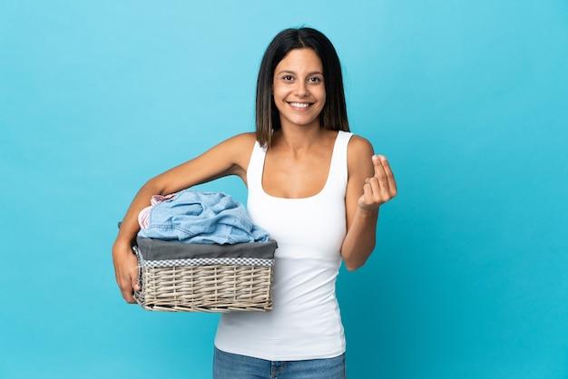 Молодая женщина, держащая корзину с одеждой, делая денежный жест