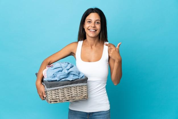 Молодая женщина, держащая корзину с одеждой на изолированном фоне, жестом показывает палец вверх