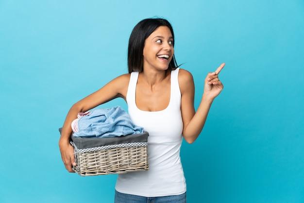Молодая женщина, держащая корзину с одеждой на изолированном фоне, намереваясь реализовать решение, подняв палец вверх
