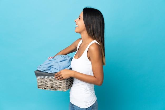 横向きの位置で笑って孤立した背景の上に服のバスケットを保持している若い女性