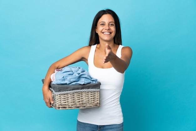 Молодая женщина, держащая корзину с одеждой на изолированном фоне, пожимая руку для заключения хорошей сделки