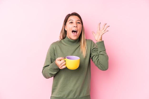 승리 또는 성공을 축하하는 커피를 들고 젊은 여자