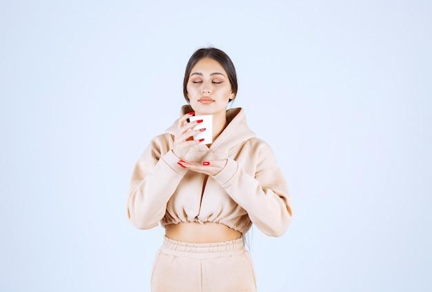 一杯のコーヒーを持って、においがする若い女性