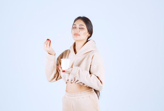Молодая женщина держит чашку кофе и нюхает