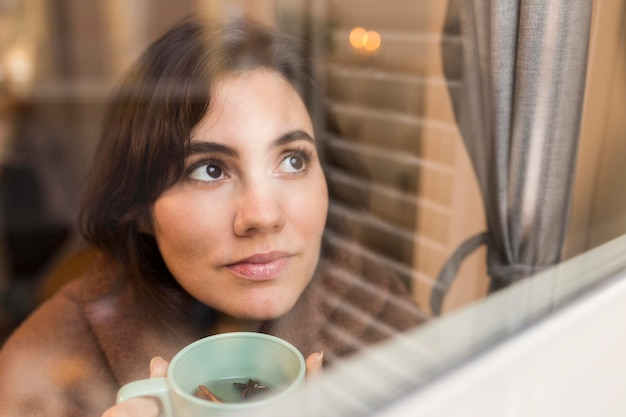 담요로 덮여있는 동안 커피 한 잔을 들고 젊은 여자