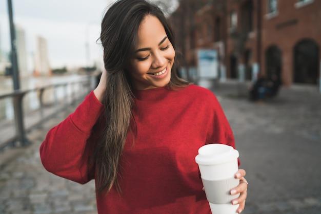一杯のコーヒーを保持している若い女性。