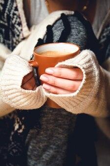 ホットコーヒーのカップを手に持った若い女性